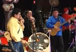 Marco Mallea is in blue playing the guitar and Andres Mallea is on the panpipes.